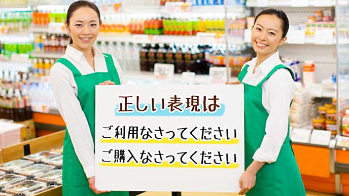 「正しい表現」が書かれたメッセージボードを正面に見せるスーパーの店員達