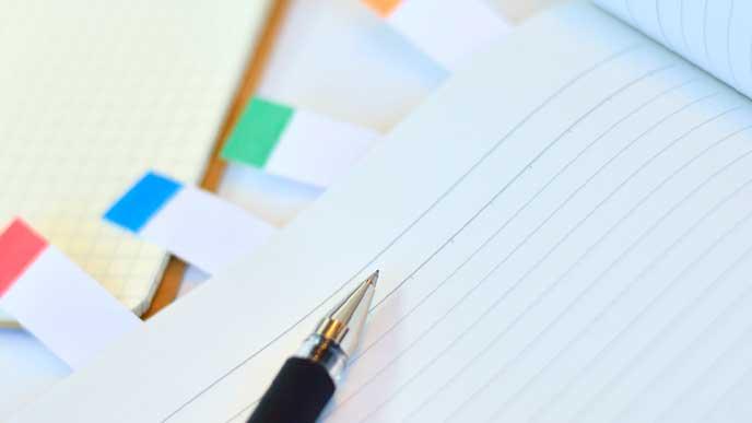 付箋をページに付けたノートとボールペンの先端