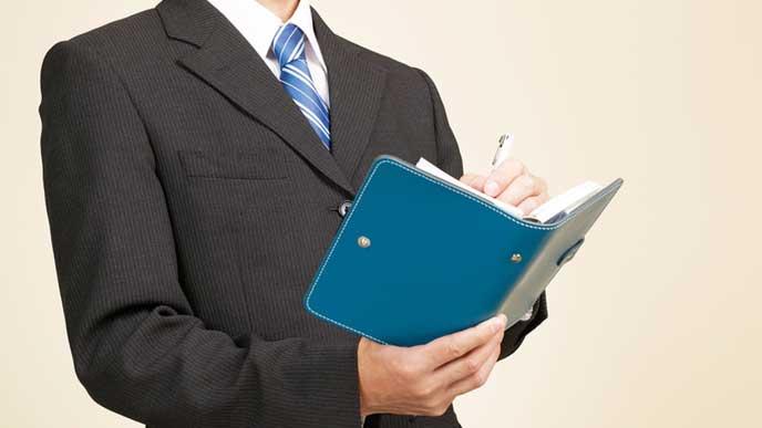 仕事のスケジュールを手帳に書くビジネスマン