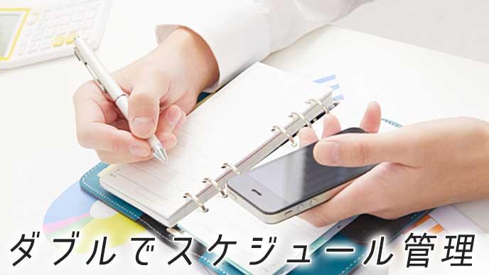 スマートホンのアプリと手帳でスケジュールを管理しているビジネスマン