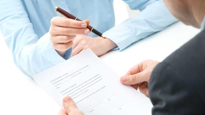 契約書のサインでお客様からペンを借りるビジネスマン
