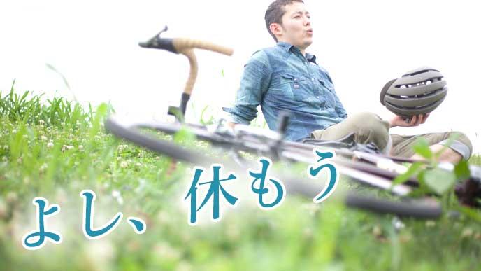 サイクリングを楽しみ、野原の上で休む男