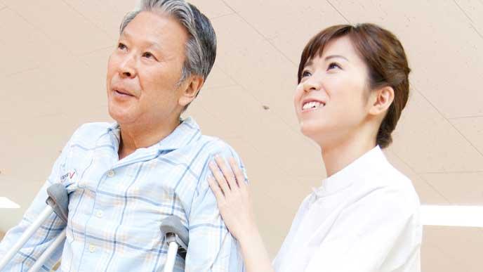 老人の肩を支えてる介護施設で働く行政保健師