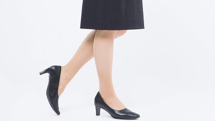 黒スーツの女性のパンプスを履いた足元