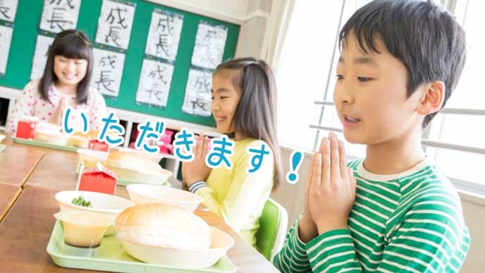 管理栄養士が作った給食に「いただきます!」と手を合わせる小学生