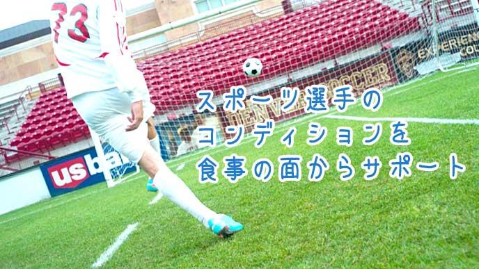 ゴールに向かってシュートを決めるサッカー選手