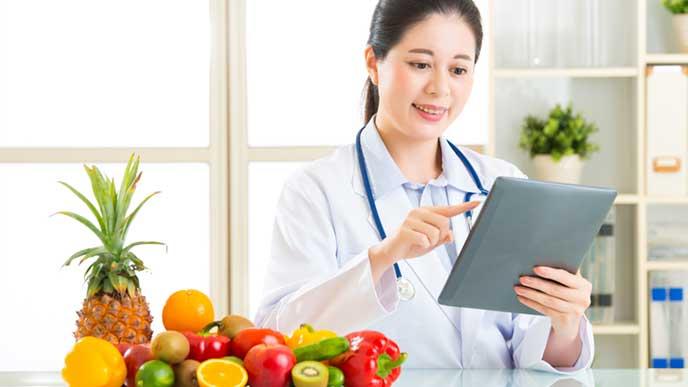 沢山ある果物の栄養をチェックしている管理栄養士