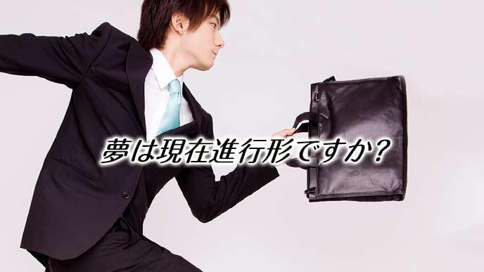 鞄を持って駆けるスーツ姿の男性