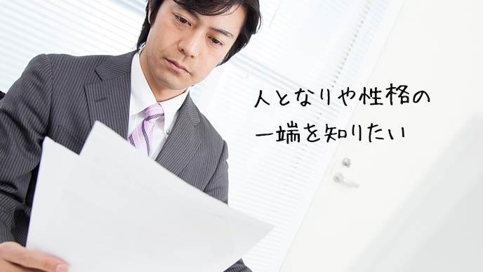 会社で応募してきたエントリーシートを見る男性