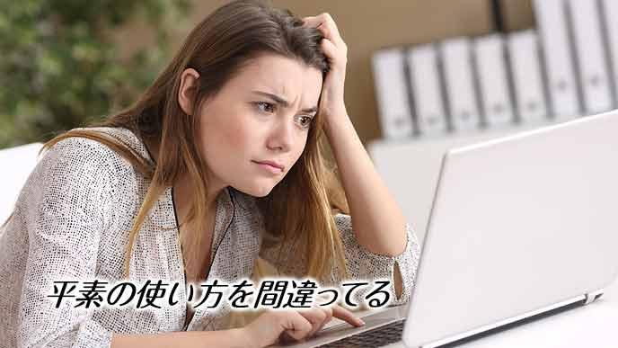会社のデスクでメールを読みながら困惑する女性