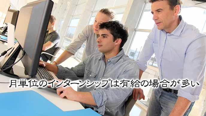 パソコンで作業する学生を見守る社員