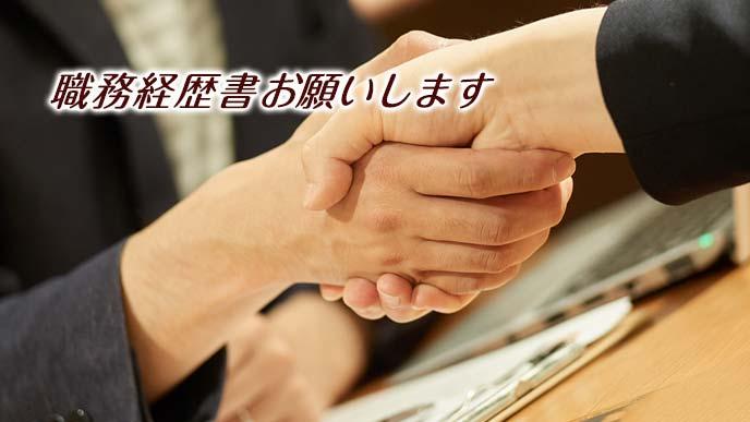 取引先と握手しながら経歴書に言及される