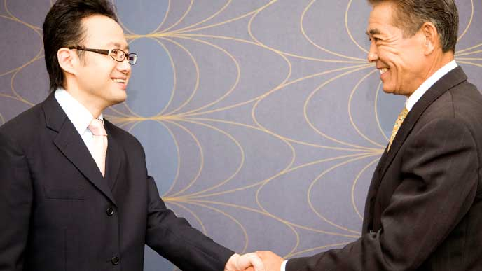 取引先と握手をするビジネスマン