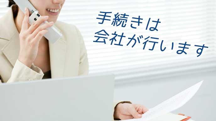 書類を見ながら電話で手続きをする会社員の女性