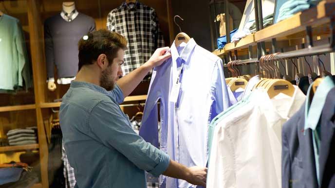 洋服屋で売られているワイシャツをじっくり見る男