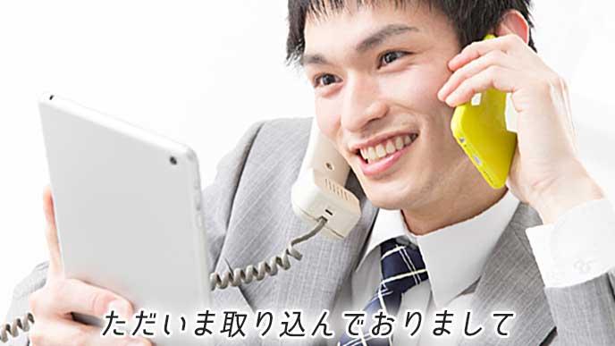 タブレットPCを見ながら電話応対と忙しいビジネスマン