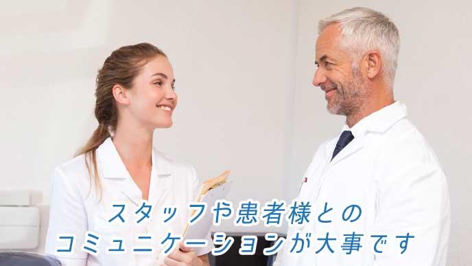 上司と笑顔で会話する歯科助手の女性