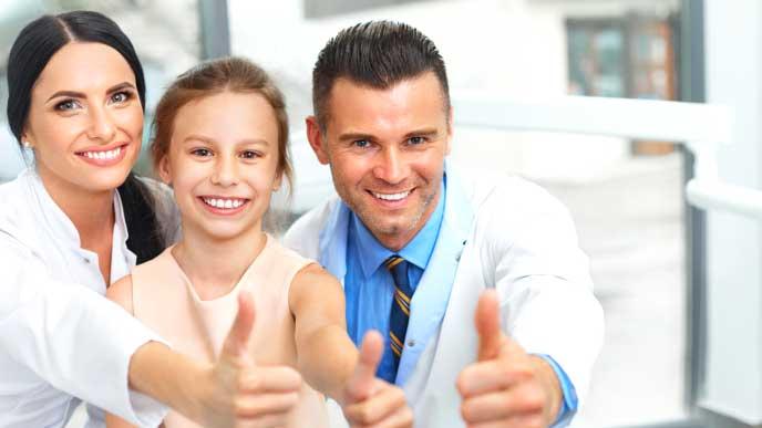 子供と一緒にサムズアップする歯科医と歯科助手