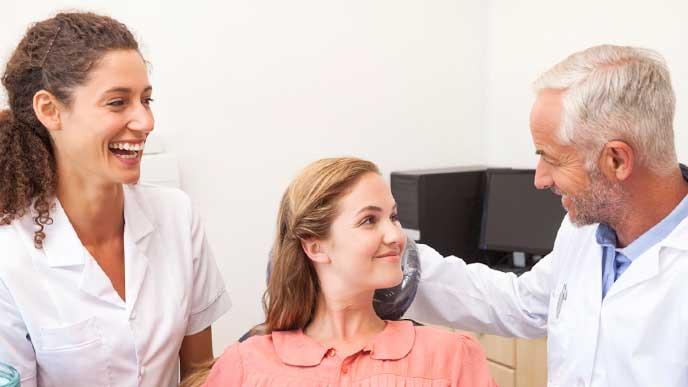 患者の虫歯が治って喜んでいる歯科医と歯科助手