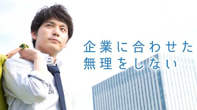 企業ビルを背景に歩くビジネスマン