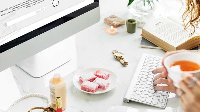 パソコンの前にお菓子の皿を置いて仕事