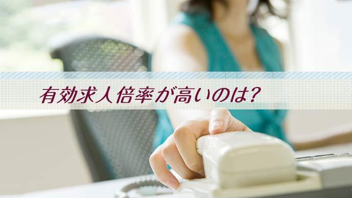 電話に手を伸ばす事務職の女性