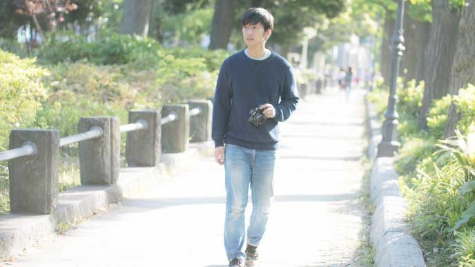 カメラを持って散歩をしている男性