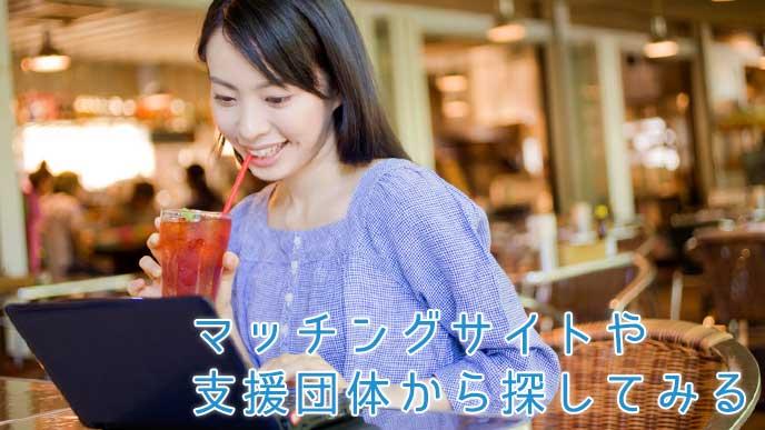 カフェでアイスティーを飲みながらインターネットをする女性