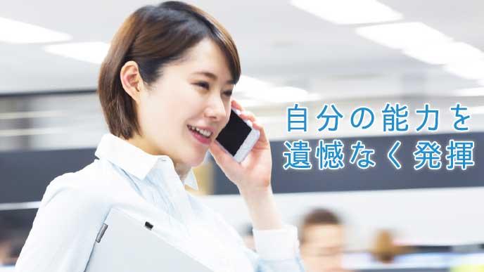 スマホで仕事の電話をする会社員の女性