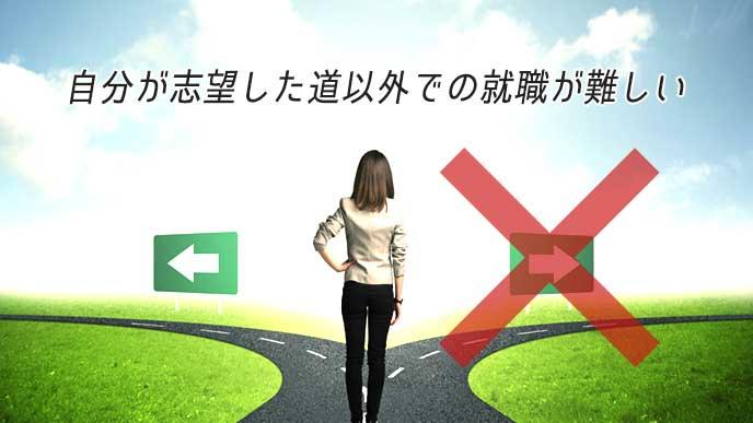 分かれ道を前に立ち止まる女性