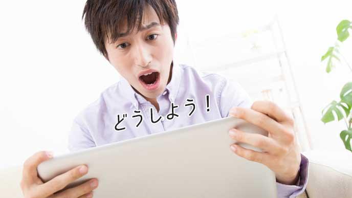 ノートパソコンを見て焦る大学生