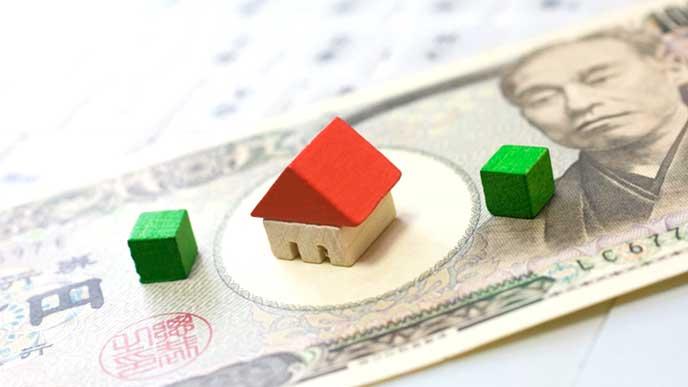 一万円札とミニチュアの家
