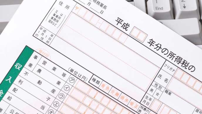 キーボードの上にある確定申告の書類