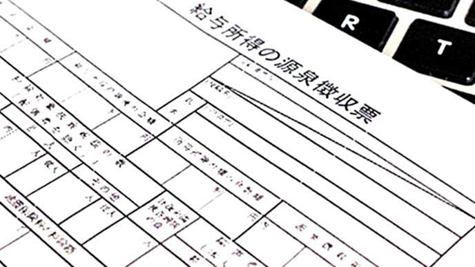 キーボードの上に置かれた源泉徴収票