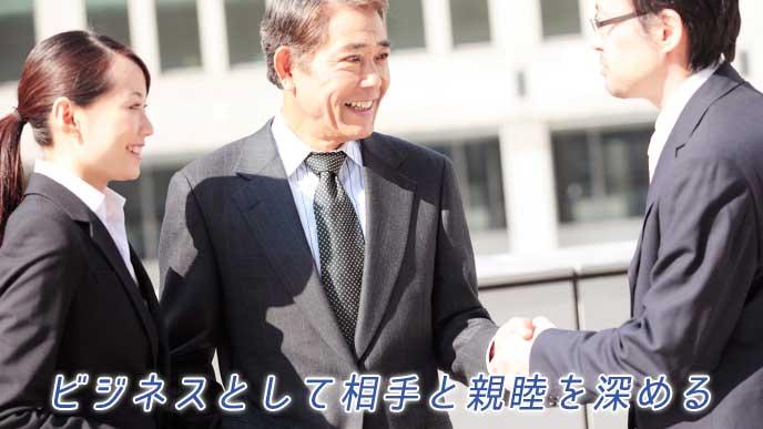 取引先の社長と握手をするビジネスマン
