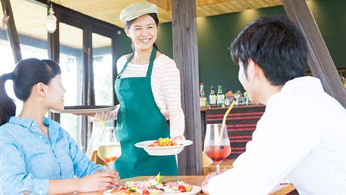お客様のテーブルに料理を運ぶレストランの店員