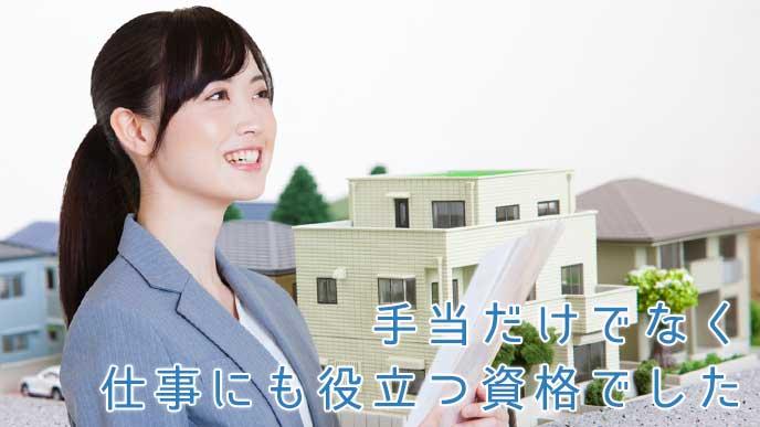 不動産の仕事をする女性と住宅地のミニチュア