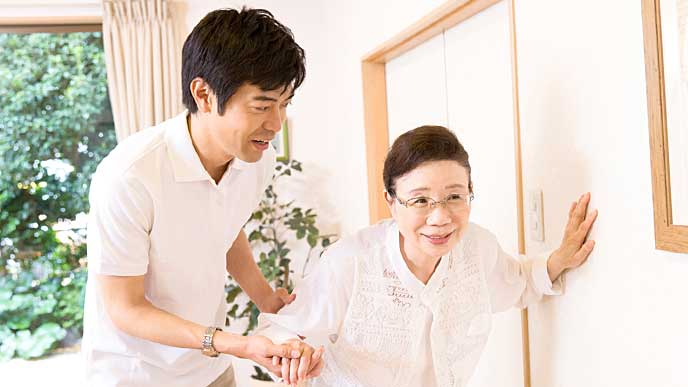お婆さんの歩行介助をする介護士の男性