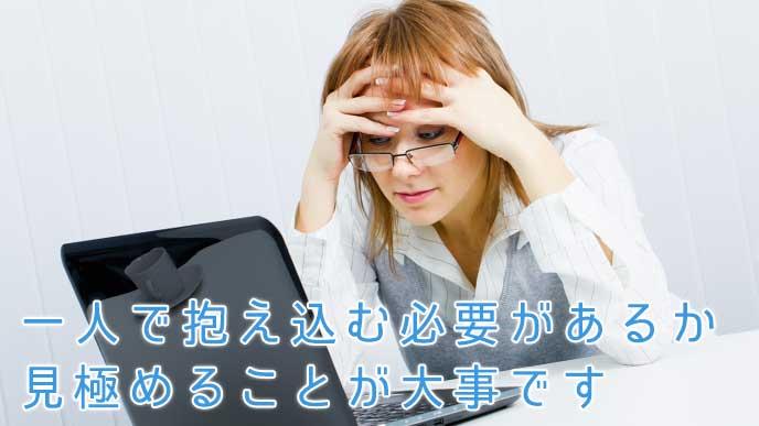 ノートパソコンを見て頭を抱える会社員の女性