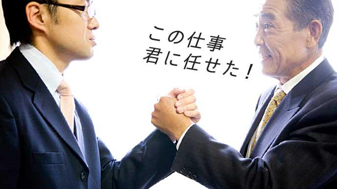 部下と力強く握手を交わす上司