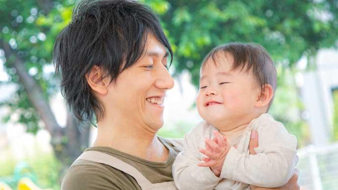 笑顔で赤ちゃんの育児をする男性