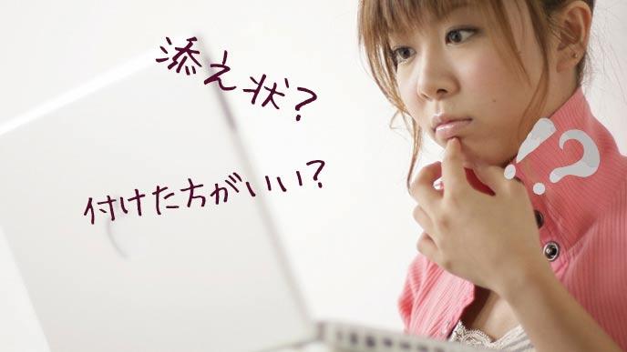 パソコンを見ながら添え状で悩む女性