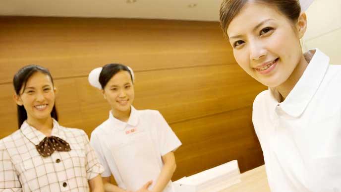 微笑んでいる2人の看護師と病院の受付の女性