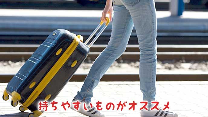 キャリーバッグを持って旅行をする女性