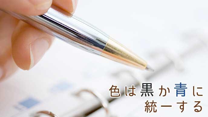 ボールペンを持った手と手帳のページ