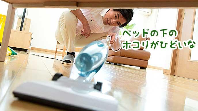 ベッドの下に掃除機をかける男性