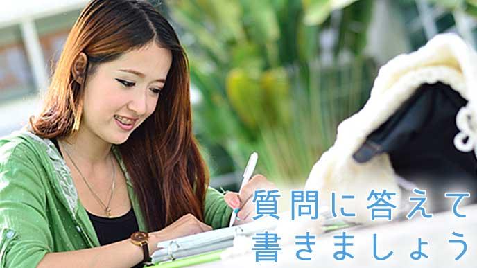 ペンを使って書いている大学生