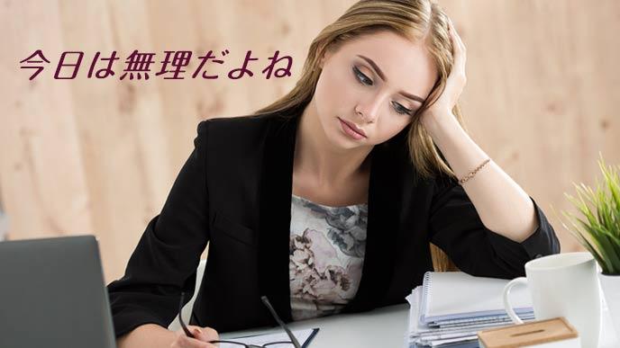 職場のデスクで考える女性