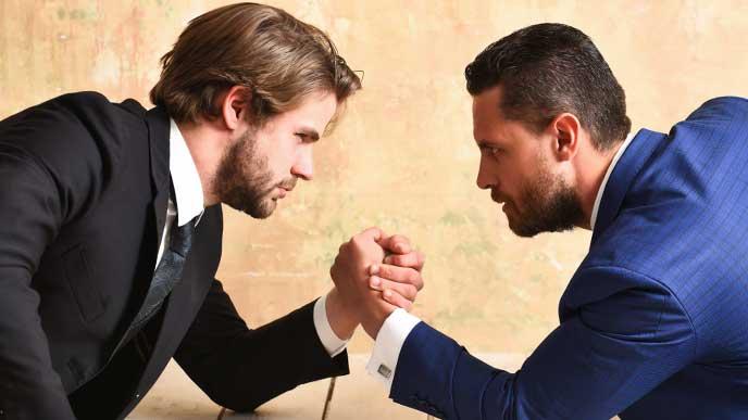 腕相撲で勝負をしているビジネスマン達