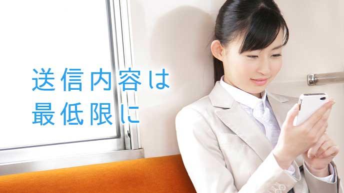 電車の中でLINEを送信する会社員の女性